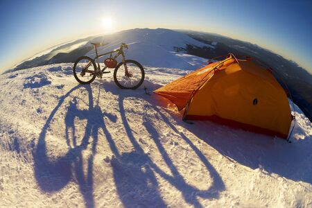 extreme unique winter ascent of the rider to the highest peak of Ukraine in Eastern Europe in a  frost with a professional mountain bike in the background of a picturesque landscape Stock Photo