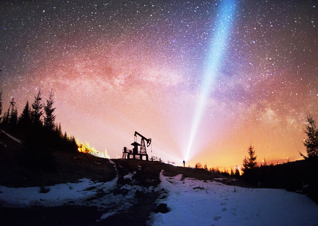 Ukrainian Carpathians, the classical technology of oil and gas extraction by electric pumps against the background of the eternal beauty of the stars of the universe of the Galaxy Stock Photo