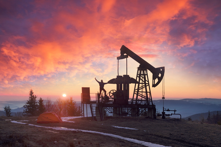In the Ukrainian Carpathians, the classical technology of oil and gas extraction by electric pumps against the background of the eternal beauty of the sunrise in the early morning