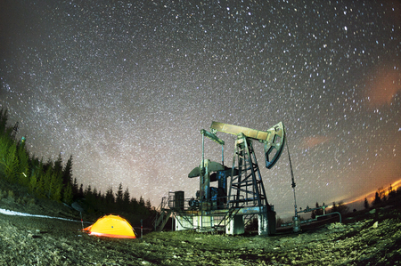 Ukrainian Carpathians, the classical technology of oil and gas extraction by electric pumps against the background of the eternal beauty of the stars of the universe of the Galaxy Stok Fotoğraf