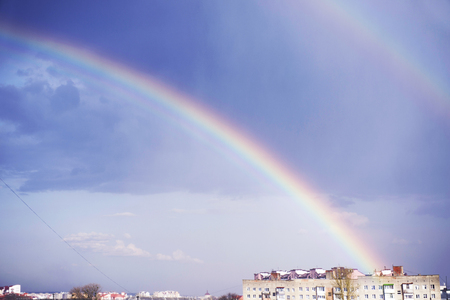 after a rain with a thunderstorm the sun quickly leaves  its bright beams pass through a rain decomposing in millions rain drops - prisms on pure colors of a solar spectrum in a rainbow Stock Photo