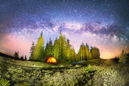 The dark mountain night shines with millions of stars over the fabulous Alpine peak in the Carpathians, the Milky Way of the Galaxy passes over a coniferous forest with a huge arc