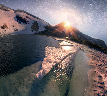In the spring a group of tourists spend the night in the snow and ice alpine lake Nesamovite Montenegrin ridge of the Carpathians, in the starry sky galaxy at moonrise Stock Photo