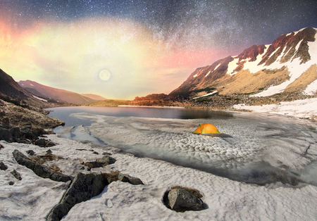 In the spring a group of tourists spend the night in the snow and ice alpine lake Berbeneskul Montenegrin ridge of the Carpathians, in the starry sky galaxy at moonrise