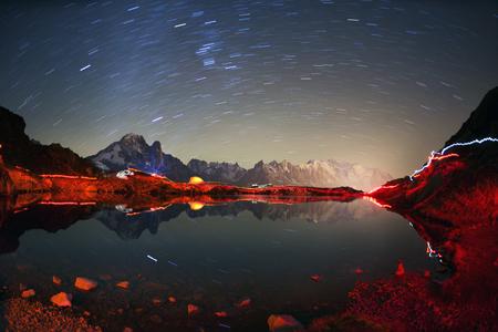 Mont Blanc Chamonix Francia autunno - la notte e il cielo stellato. Lac Blanc bella notte sullo sfondo delle ripide vette delle Alpi con i ghiacciai. Gli scalatori aggirano il lago con le lanterne.
