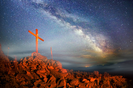 Cross on Mount Strymba wooden raised to the glory of God, Jesus Christ. Night light lighting a fire on a background of mountains alpine vegetation stones under the stars of the Milky Way 写真素材