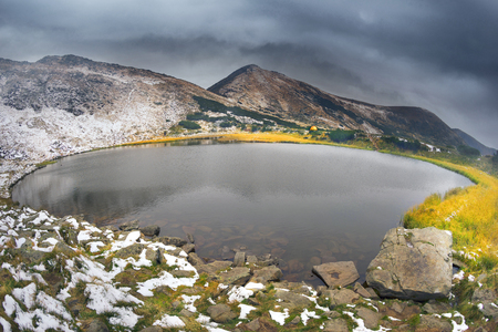 Lake Nesamovite ( Nesamovitoe) under the mountain Turkul in Chernogora Ukraine during a snowstorm in September. Cold and snowfall is dangerous for tourists in the autumn in the mountains Imagens
