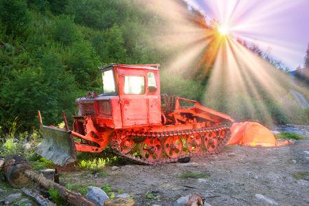 Photo-artist unusually photographed with the help of colored lanterns in a mountain hike. An old caterpillar tractor of the Soviet Union is abandoned in the mountains of Ukraine