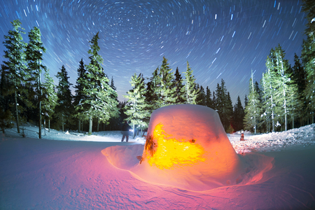 Tourists Ukraine on a hike along the Black Mountain near the frozen lake Maricheyka built an Eskimo snow house needle and spend the night under the starry sky of the Galaxy