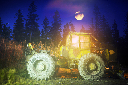 An ancient tractor at the top of the mountain for transportation of coniferous forest is illuminated by a photographer of various lights in the moonlit night in the Carpathians as an art object