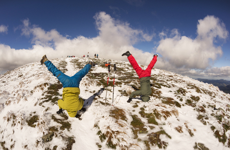 The cheerful sports people of the tourist rejoice in the autumn winter ascent to the high mountains of the Carpathians of Ukraine Petros and Goverla, standing on their heads upside down
