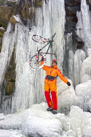 An interesting bicycle trip of a climber - an athlete through the mountains with a carbon-fiber mountain bike passes through a snow-covered icy canyon covered with gigantic ice icefalls