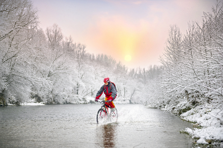 Snowy whirlwinds in a bike ride with a Christmas holiday in the wild Ukrainian river. Hurricane winter wind carries snow whirlwinds on fast ice riders of Ukraine, to the Carpathians.