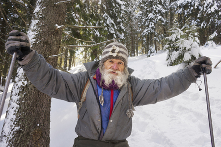 In winter, an interesting original traveler lives in the Carpathians-a very old, almost a hundred-year-old grandfather, who in his youth ascended to many complex peaks Stock Photo