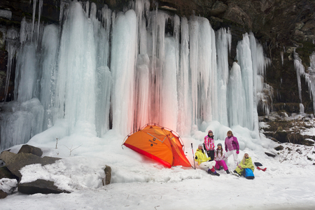 Ukraine, Mykulychyn, March 9, 2018: Alpine wild canyon in severe frost streams of water froze on high rocks and tourists travelers admire the unique spectacle in Europe the Carpathian mountains Imagens