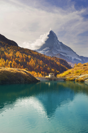 Autumn larches on the background of the Matterhorn and autumn in the Alps. The clear water of the mountain lake Stellisee is a local landmark and a bright beautiful landscape.