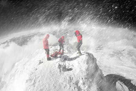 A rescue squad of European climbers is training in rescuing the victims on ice rocks during a foggy storm on the Black Mountain in the Carpathians. Severe frost and wind on the alpine peaks