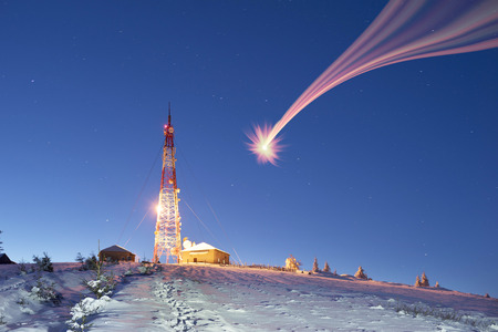 At the top of the Alpine mountain stands a radio television tower mobile signal translator. In severe frost before Christmas, the design looks like a New Year tree hi-tech