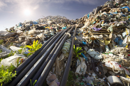 huge landfill site, a special device collects and pumps methane and other gases into storage. Gas through rubber pipes goes to tanks, alternative energy