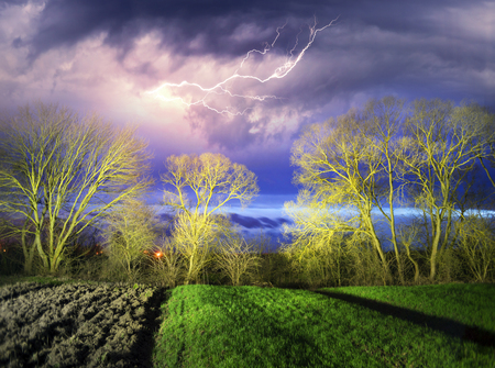 Field of young winter wheat at night, lit by a strong thunderstorm with lightning and lights of passing cars with highways, lights of the city in the distance