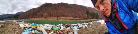 Ukraine, Kolochava, March 21, 2019: A tourist photographed with a mobile phone Xiaomi a panorama of ecological disaster - the river carries plastic waste to Europe