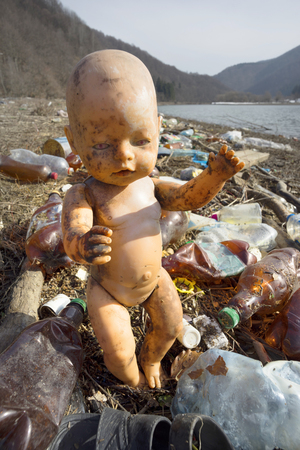 traveler in Ukraine, Kolochava village, photographed a panorama of ecological disaster - in the spring the river carries plastic trash to Europe, abandoned by non-cultural people. Doll symbolizes trouble