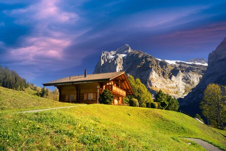Shepherds' houses over the town of Chamonix under the ridge of the high Alps near Mont Blanc, old traditional wooden huts for cows and sheep
