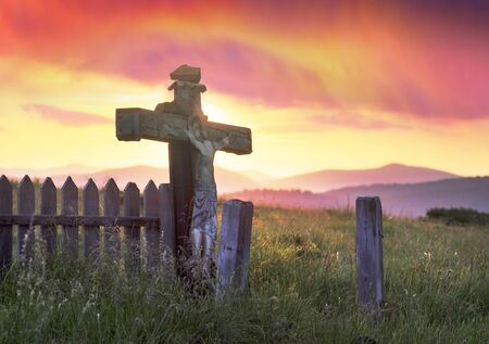 wooden cross in the Carpathians after a thunderstorm with lightning and thunder over the tops of the ridges, with strong wind and rain - there comes a clear beautiful morning Stockfoto
