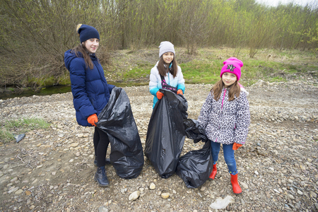 Ukraine, Ivano-Frankivsk, April 13, 2019: Children volunteers scavenge in the green area of the city on the embankment of the river Bistritsa Editorial