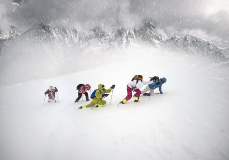 group of inexperienced climbers fell in bad weather on the Alps and cannot climb to the top. Strong winds, snow and frost are dangerous for tourists.