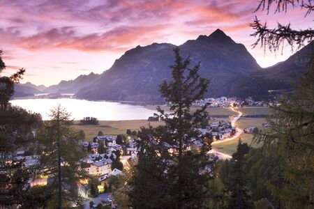 Silvaplana in Switzerland is a beautiful chain of lakes surrounded by picturesque rocky peaks. The starry sky of the Galaxy and the lights of cities and villages below are beautiful