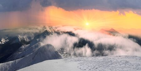 Montenegro's watershed ridge in foggy clouds after a snowstorm. Beautiful gentle streaks of fog over the wild peaks of the Carpathians.