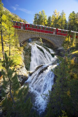 Swiss electric trains pass mountain alpine gorges over beautiful stone bridges over stormy clean rivers and waterfalls, among a golden autumn forest. Imagens