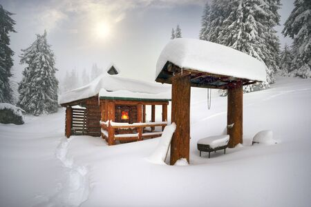 Heavy snowstorm in the Alps. The cyclone brought heavy rainfall to the mountains, a fast wind sweeps the house of tourists and hunters who rise to the peaks