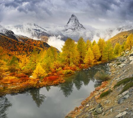 Matterhorn, across from Lake Grindjisee above the city of Zarmatt, is a famous landmark surrounded by larch trees and cliffs, one of the symbols of Switzerland.