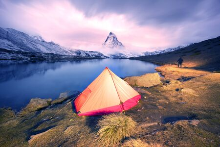 Matterhorn, across from Lake Stellisee above the city of Zarmatt, is a famous landmark surrounded by larch trees and cliffs, one of the symbols of Switzerland. Lone traveler's tent.