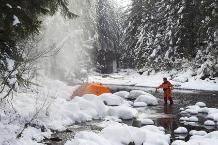 Tourist tent in a snowy canyon. Extreme mountain equipment gives comfort and safety in a tourist trip in winter in the cold. Heavy snowfall covered the alpine river.