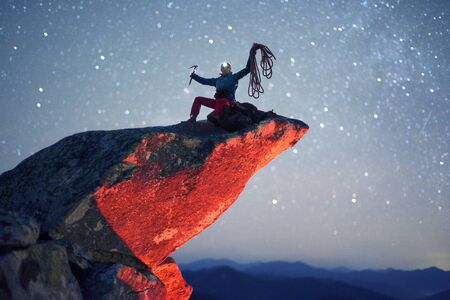 A symbolic picture with a climber on a sharp stone rock with a rope and an ice ax on a fantastic alpine mountain landscape with stars in the Himalayas