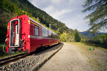 Switzerland, Poschiavo, October 10, 2019: Railroad train on the shore of Lake Poschiavo against the backdrop of alpine peaks. It connects the cities of St. Moritz in the canton of Graubunden, Switzerland and Tirano, in the province of Sondrio, Italy, thro