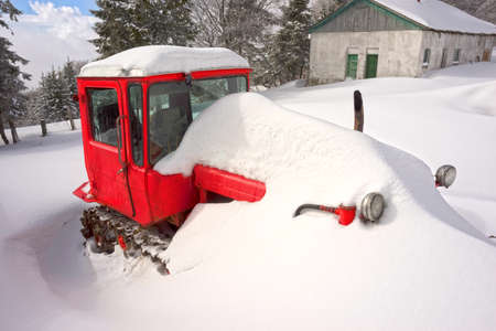 Severe frost and a blizzard brought an old rural tractor high in the mountains. It is used to overcome snow drifts and avalanches.