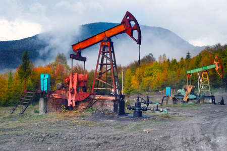 Oil gas traditional old pump platform for mining production of minerals - oil and gas in the autumn mountains of Europe after rain and fog. 版權商用圖片