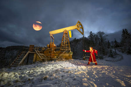 Santa Claus brought a bag of gifts under an oil pump with the flag of Ukraine in the winter mountains of the Carpathians to oil and gas workers. Have fun celebrating New Year 版權商用圖片