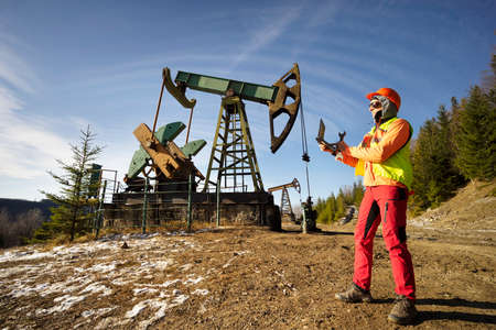 Ancient oil and gas field in the Ukrainian Carpathians, begun under Austria-Hungary, Poland. Gas worker engineer oil worker checks the operation of the pipeline and pump at the beginning of winter.