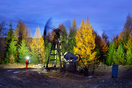 An ancient oil and gas field in the Carpathians, Ukraine - Romanian pumps work at night on mountain slopes.