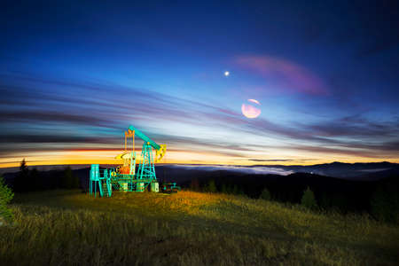 classic Romanian pumps work at night on the mountain slopes of the Carpathians, Ukraine. The constellations of the stars and the Milky Way symbolize the antiquity of the Earth's mineral resources.