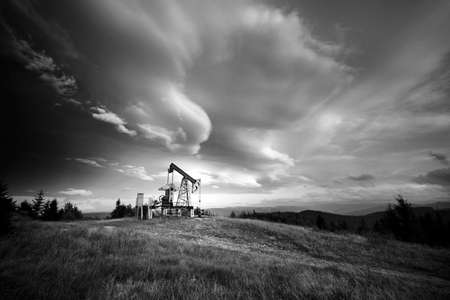 Oil gas traditional old pump platform for mining production of minerals - oil and gas in the autumn mountains of Europe after rain and fog. Classic black and white photography.