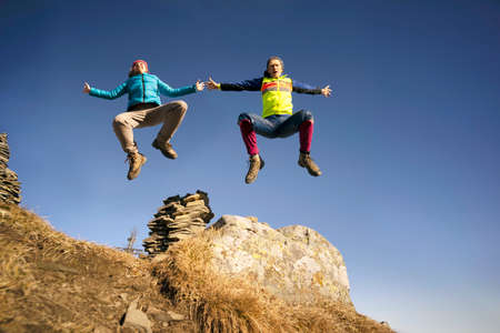 Man and woman jumping to the top.