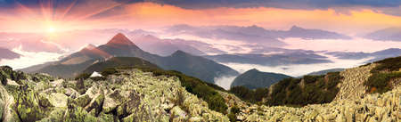 Morning dawn after rain with fog on the alpine stone wastelands of the Gorgan of the Carpathians of Eastern Europe. White tent glows in the rays of dawn over a misty valley