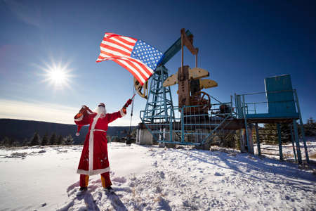 Santa Claus near oil pump with a US flag in America's winter mountains. 版權商用圖片
