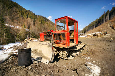 Spring has come in the mountains after winter and heavy tracked tractors are pulling large tree trunks through the mud. Wood is necessary for the country, but harm to ecology and problems to tourism 版權商用圖片